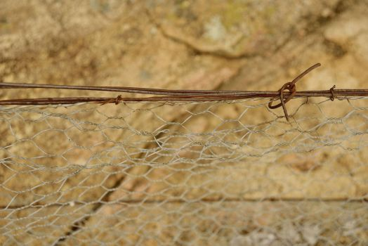 Barbwire Hanging Over Rock by Rhyton