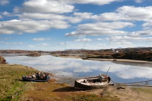 old fishing boats beached on Donegal beach by morrbyte