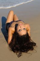 Sarah reclining on beach by wildplaces