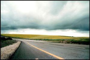 Storm gathering over open road by taftaras