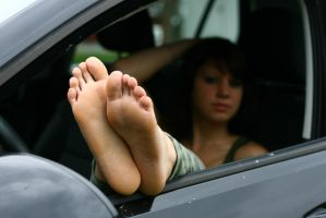 Franzi showing her soles of feet out of a car by foot-portrait