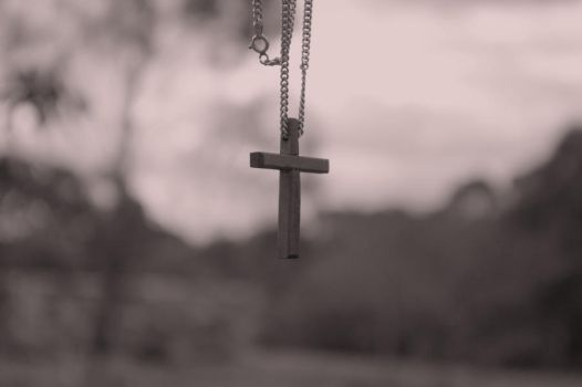 cross hanging from a wire fence by Veruca1280
